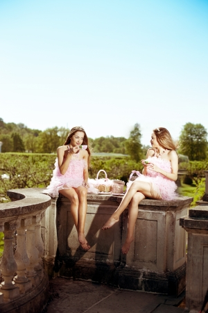 Beautiful twins whith cups of tea or coffee photo