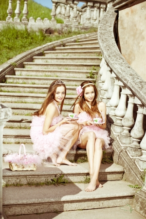 teenager nude: Beautiful twins whith cups of tea or coffee