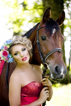 red horse: Woman in red dress with bright makeup on the horse outdoors Stock Photo