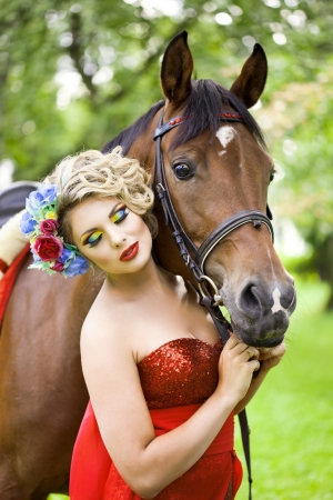 Woman in red dress with bright makeup on the horse outdoors photo