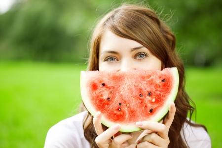 Beautiful woman with juicy watermelon in hands