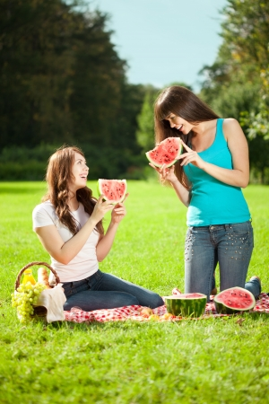 Two young women on a picnic with watermelon photo