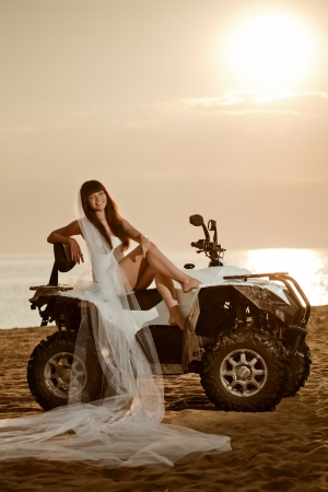 Beautiful bride sitting on a quad bike on the beach at sunset photo