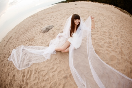 Beautiful bride in a short dress with a long veil on the beach at sunset photo