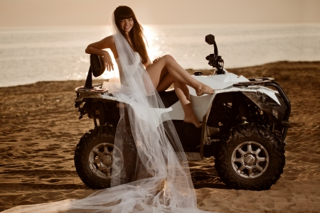 Beautiful bride sitting on a quad bike on the beach at sunset Stock Photo - 20590205