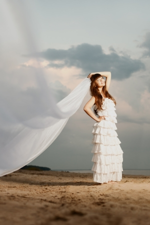 Beautiful bride in a long dress with a long veil on the beach at sunset photo
