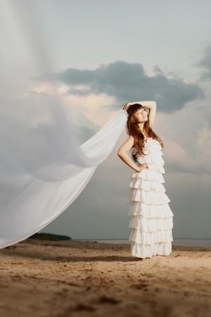 Belle mari?dans une robe longue avec un long voile sur la plage au coucher du soleil Banque d'images