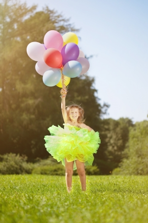 kids dress: Child with a bunch of balloons in their hands  Stock Photo