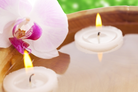 Spa therapy, flowers in water, on a bamboo mat. Stock Photo