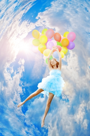 flying woman: Woman holding balloons against sun and sky