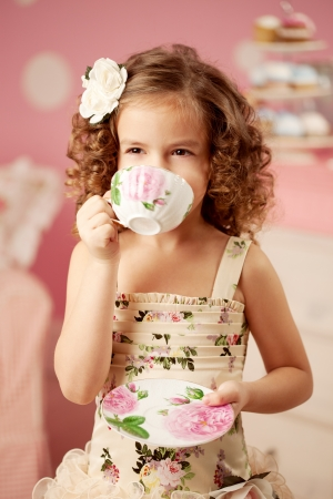 party dress: Little cute and sweet girl with tea Stock Photo