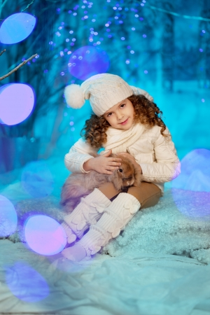 Little cute winter girl with rabbit photo