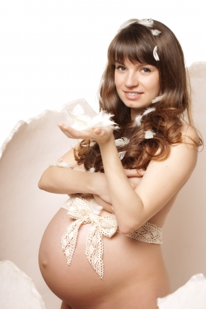 Beautiful pregnant woman in an egg