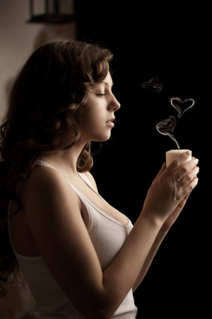 Beautiful woman with a candle in love on a black background photo