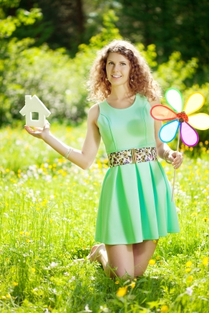 garden key: Young woman with hose model and key in a lush garden Stock Photo
