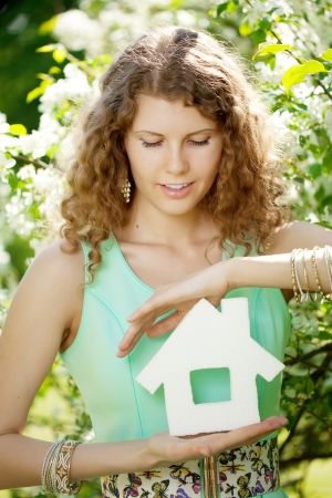 Young woman with hose model and key in a lush garden photo