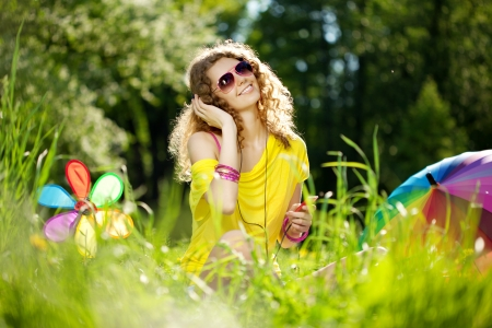 Beautiful young woman listening to music in the park
