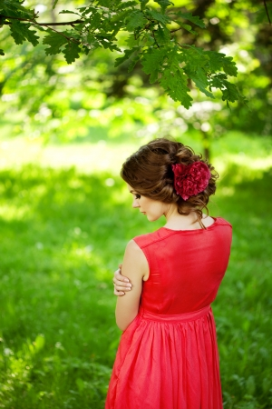 girl in red dress: Beautiful woman with a flower in the hairstyle outdoors Stock Photo