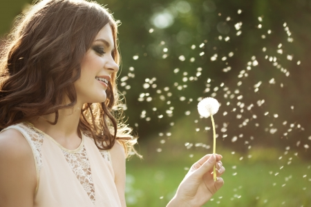 girl holding flower: Beautiful young woman blowing a dandelion  Stock Photo