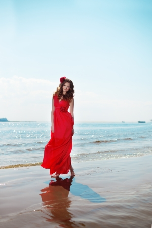 Beautiful woman in a bright red dress by the sea photo