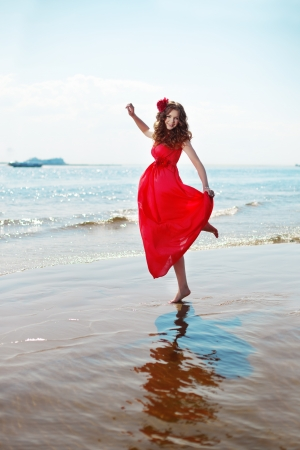 girl in red dress: Beautiful woman in a bright red dress by the sea