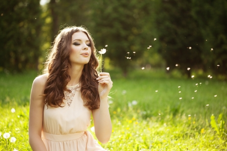 dandelion wind: Beautiful young woman blowing a dandelion