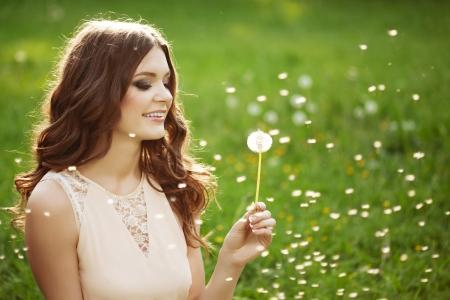 Beautiful young woman blowing a dandelion