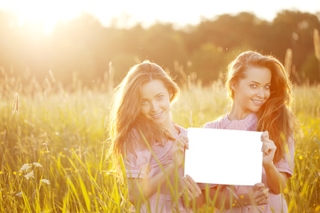 Smiling twins holding white blank poster  outdoors photo