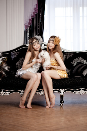Two beautiful stylish womans with a rabbit photo
