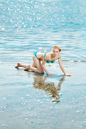 Beautiful slim woman on the beach by the sea photo