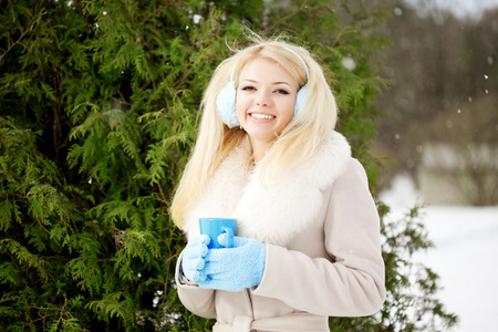 Young woman with a cup of hot drink in winter wood photo