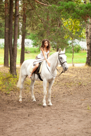 Beautiful woman on a horse. Horseback rider, woman riding horse photo
