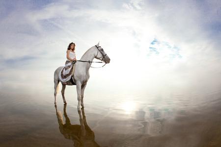 Beautiful woman on a horse. Horseback rider, woman riding horse on beach photo