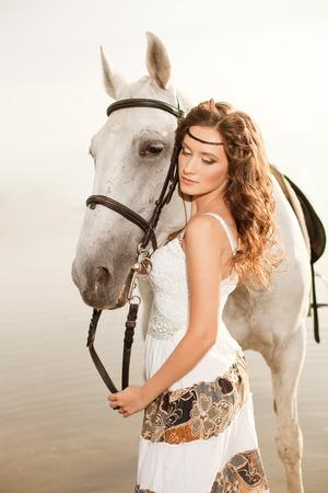 girl on horse: Beautiful woman on a horse. Horseback rider, woman riding horse on beach.