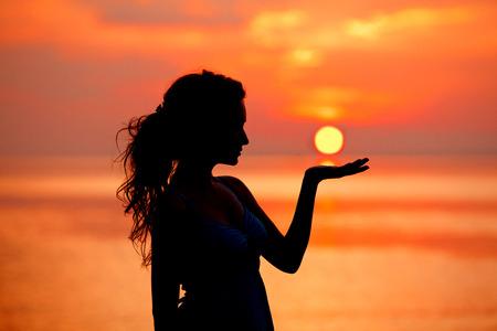 海の夕日で楽しんで幸せな自由な女。手のひらに日没、日の出の太陽を背景にシルエット