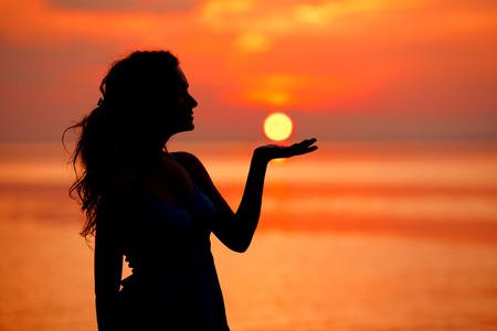 Glückliche freie Frau genießt im Meer Sonnenuntergang. Gegen den Sonnenuntergang, Sonnenaufgang abhebt. Sonne auf der Handfläche Standard-Bild - 26652319