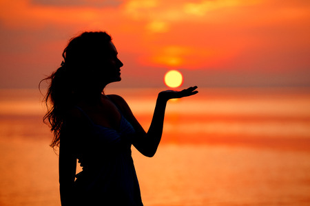 Happy free Woman enjoying in Sea Sunset. Silhouetted against the sunset, sunrise. Sun on the palm Banco de Imagens