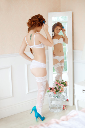 Pretty young woman in lingerie in the interior of the room  photo