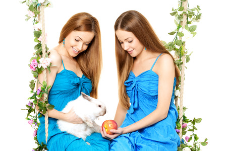 twin sister: Two women on a swing on white background with rabbit
