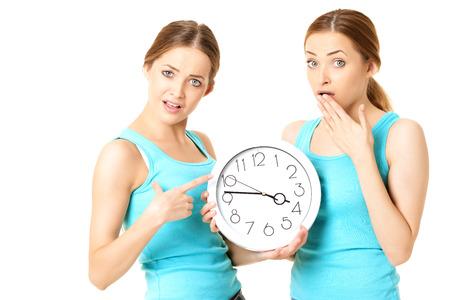gemelas: Dos mujeres sonrientes que sostienen un reloj - aislados en un fondo blanco
