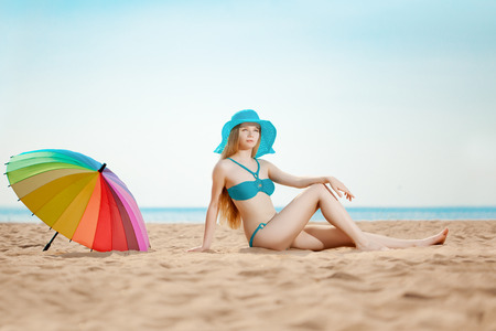 Beautiful slim woman on the beach by the sea photo