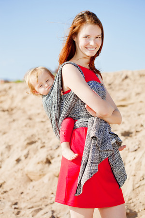 adult breastfeeding: Beauty woman with a baby in a sling. Mom and baby. Mother and child. Stock Photo