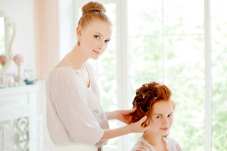 detail invitation: Hair stylist makes the bride before the wedding Stock Photo