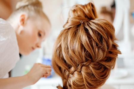 hair dresser: Hair stylist makes the bride on the wedding day