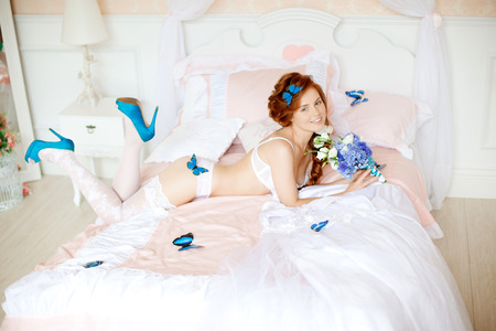 Beautiful young woman lying on the bed with flowers photo