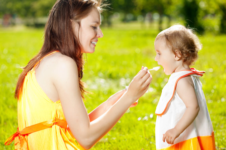 Mother feeds baby girl outdoors in the grass photo