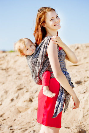 Beautiful woman with a baby in a sling. Mom and baby. Mother and child. photo