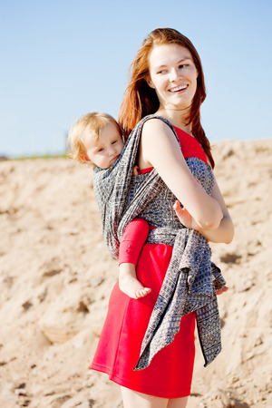 Beautiful woman with a baby in a sling. Mom and baby. Mother and child photo