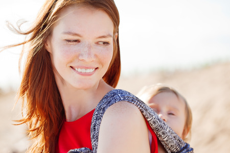 carrier: Beautiful woman with a baby in a sling. Mom and baby. Mother and child.