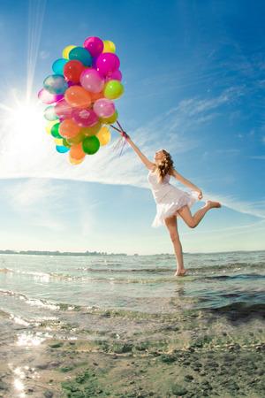 美しさ若い多色虹風船が空の手の中でスタイリッシュな女性。自然に肯定的な女の子。女性の屋外を楽しむ笑顔。